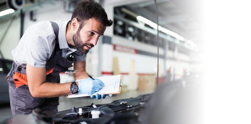 mechanik sprawdzający silnik samochodu