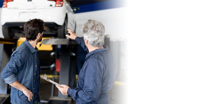 dwóch mężczyzn patrzących nasamochód stojący napodnośniku